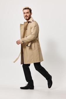 Un uomo con un cappotto beige cammina di lato con gli stivali dei pantaloni su uno sfondo chiaro