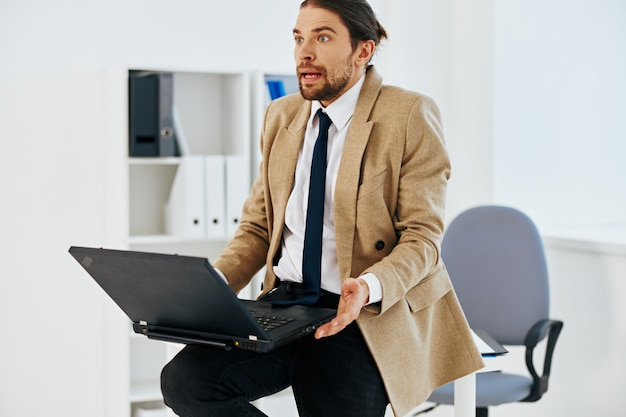 Uomo in giacca beige dirigente d'ufficio di lavoro laptop ufficiale