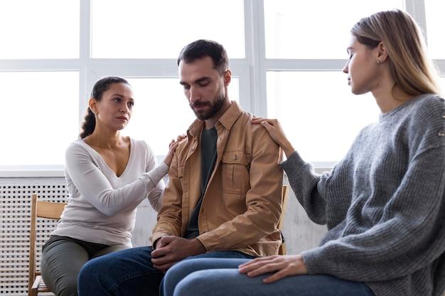 L'uomo viene consolato dalle donne in una sessione di terapia di gruppo