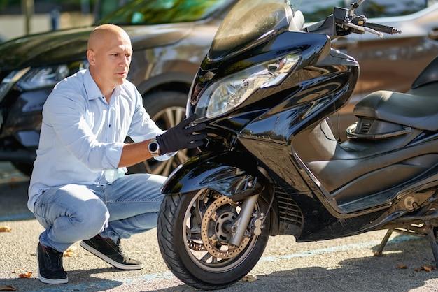 Motociclista dell'uomo che ripara il motociclo dello scooter alla via.