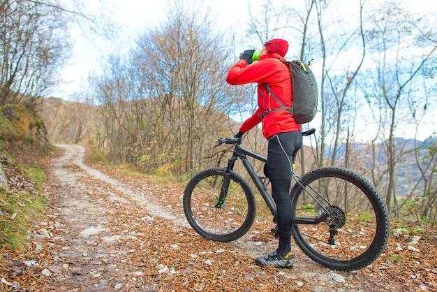 L'uomo in bicicletta in montagna riposa e beve l'acqua