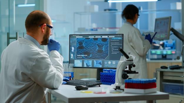 Biologo uomo che controlla le informazioni sul dna digitando su pc in un moderno laboratorio attrezzato. scienziati che esaminano l'evoluzione del vaccino nel laboratorio medico utilizzando strumenti chimici ad alta tecnologia per la ricerca scientifica.