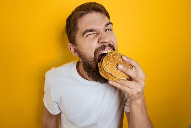 Uomo che morde da un delizioso hamburger