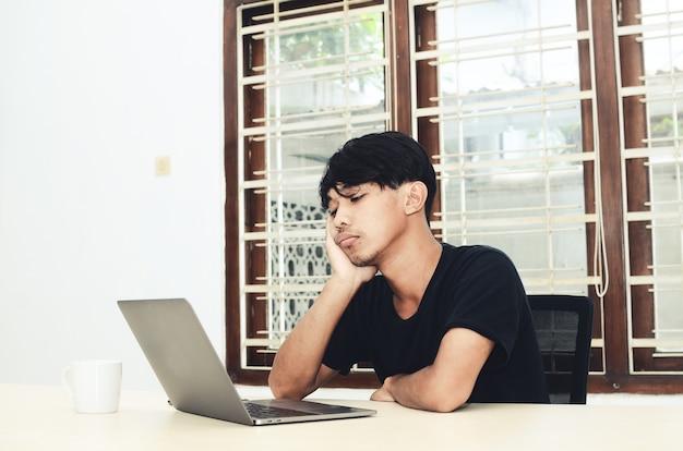 L'uomo con una maglietta asiatica nera si sedette davanti al laptop con un'espressione delusa