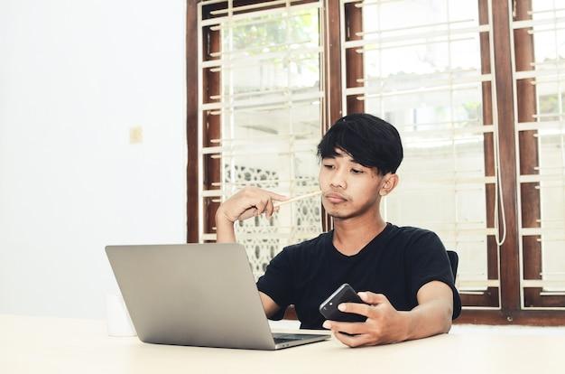L'uomo con una maglietta asiatica nera si sedette davanti al laptop con un'espressione triste
