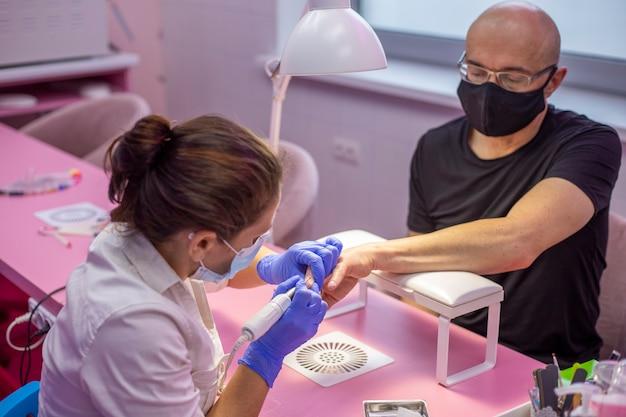 L'uomo in maschera facciale nera sta avendo manicure in salone. manicure in tempo di pandemia