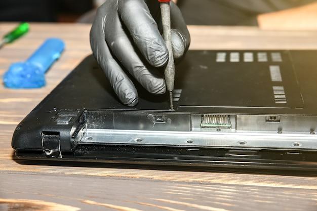 L'uomo in guanti neri sta riparando un computer portatile. ragazzo in possesso di un cacciavite. l'operatore del centro servizi sta risolvendo i problemi.