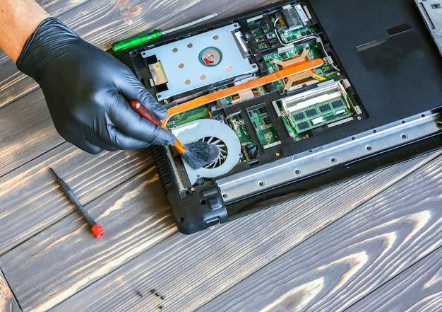 L'uomo in guanti neri sta riparando un computer portatile. operaio del centro servizi che pulisce la polvere.