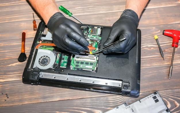 L'uomo in guanti neri sta riparando un computer portatile. operatore del centro servizi che risolve il problema.