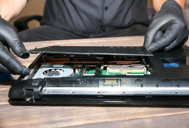 L'uomo in guanti neri sta riparando un computer portatile. l'operatore del centro servizi sta risolvendo i problemi.