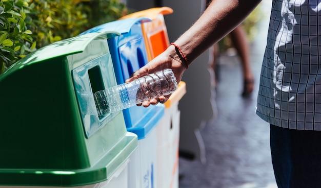 La mano nera dell'uomo che getta una bottiglia d'acqua di plastica vuota nel cestino dell'immondizia