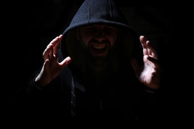 Uomo con cappuccio nero e fumo su sfondo nero
