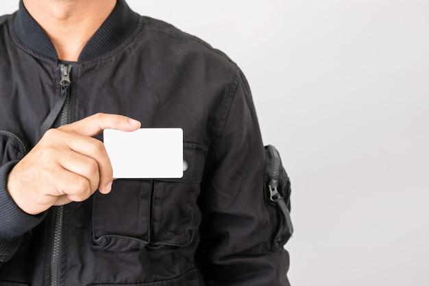 Uomo in giacca nera che tiene la patente di guida in bianco