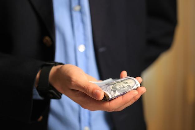 Uomo in una giacca nera che tiene i dollari in mano