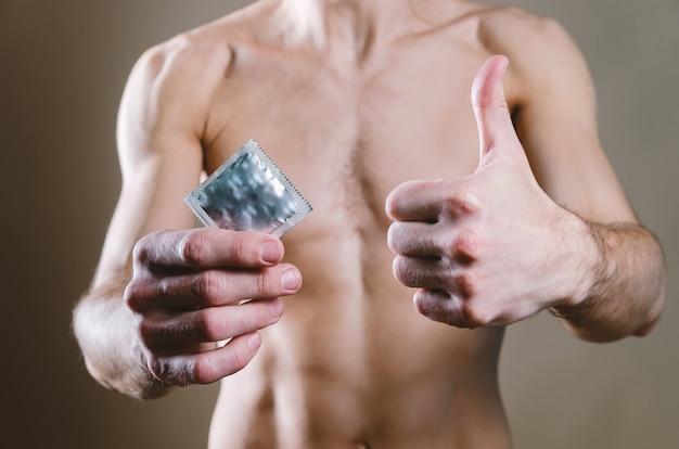L'uomo in jeans neri tiene in mano un preservativo e con l'altra mano mostra il dito verso l'alto,