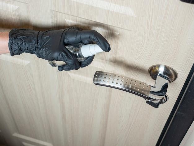 Un uomo in guanti di lattice nero spruzza antisettico sulla maniglia della porta.
