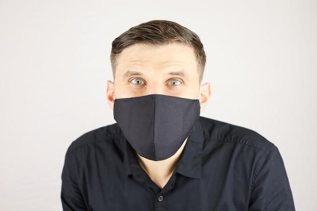 Un uomo con una maschera medica nera guarda la telecamera su uno sfondo bianco
