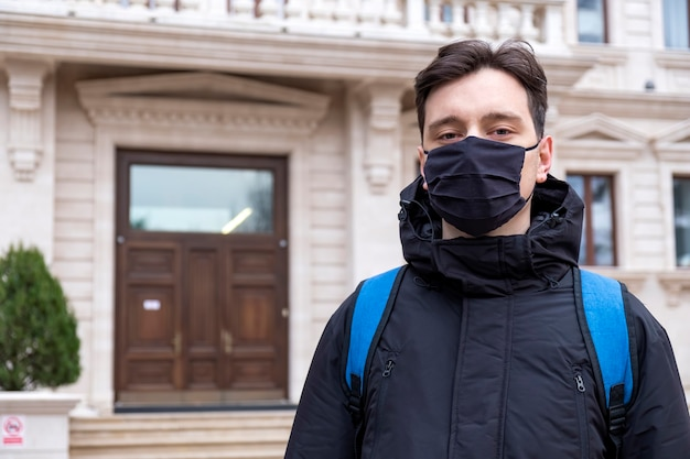 Un uomo in maschera medica nera e una giacca invernale con zaino blu che esamina la macchina fotografica, edificio e cespugli sullo sfondo a chisinau, in moldova