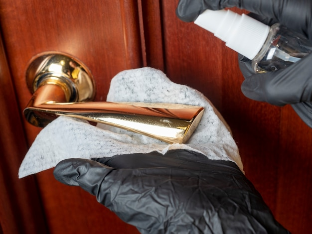Un uomo in guanti protettivi neri gestisce la maniglia della porta con un disinfettante all'interno della stanza. protezione antivirus, trattamento degli ambienti, disinfezione.