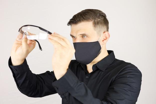 Un uomo in una maschera protettiva nera esamina gli occhiali medici su sfondo bianco