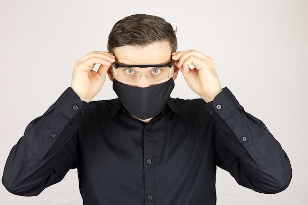 Un uomo con una maschera protettiva nera ha messo le mani dietro gli occhiali medici su uno sfondo bianco