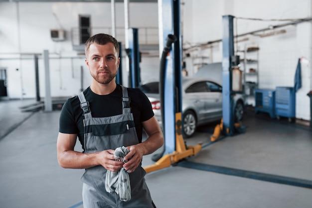 L'uomo in camicia nera e uniforme grigia si trova in garage dopo aver riparato l'auto rotta