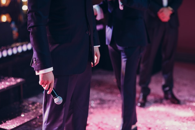 Uomo in abito nero che tiene il microfono in mano giù