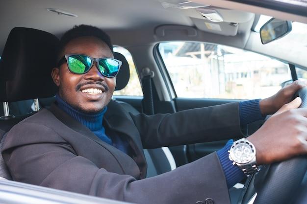 Uomo in abito nero seduto al volante con sorriso e felice