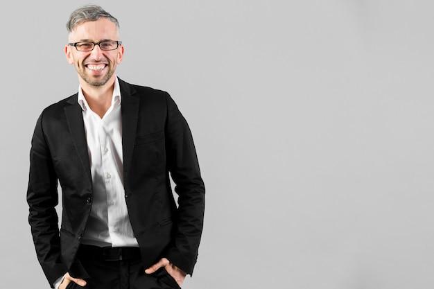 Uomo in vestito nero con gli occhiali e copia spazio