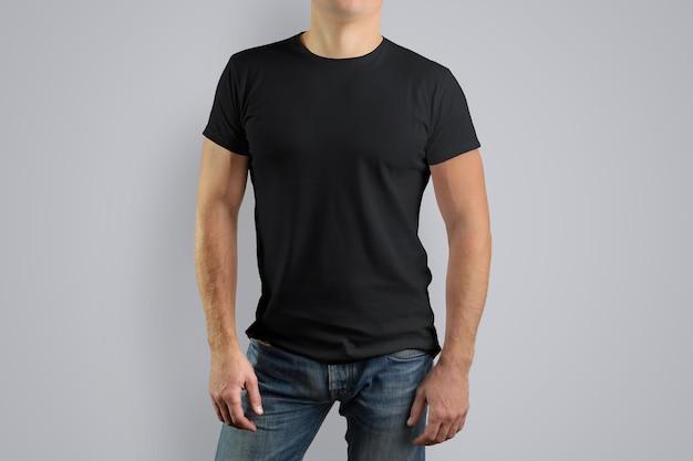 L'uomo con una maglietta nera è isolato su un muro grigio.