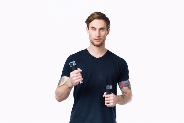 Un uomo in una maglietta nera con manubri nelle sue mani sport fitness model