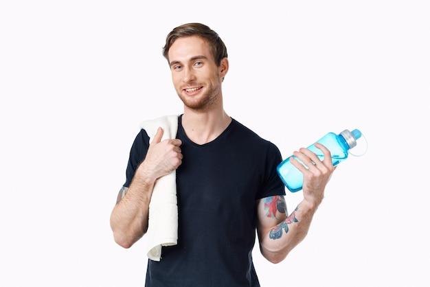 Uomo in maglietta nera con una bottiglia d'acqua in mano e un asciugamano sulla spalla vista ritagliata