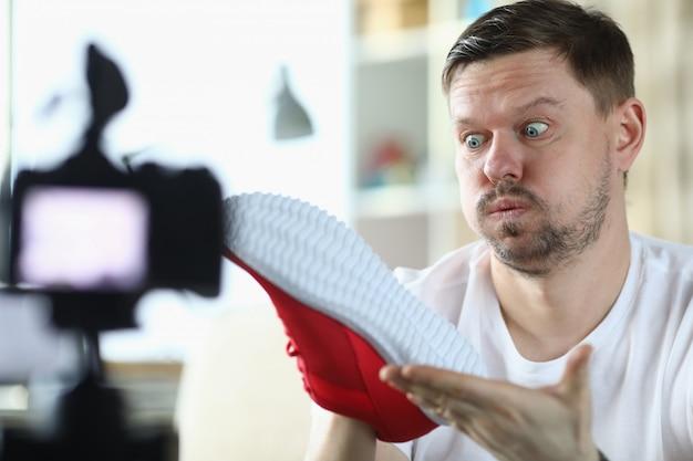 L'uomo blogger guarda la sneaker nella fotocamera frontale