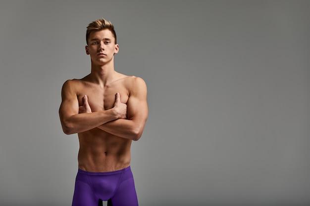 Uomo biondo nuotatore, ritratto a mezzo busto su sfondo grigio, copia spazio, motivazione per lo sport, raggiungimento del successo, banner pubblicitario.