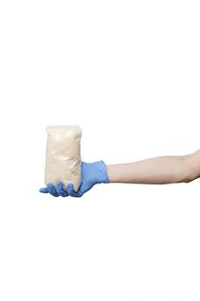 Uomo in guanti blu che tengono pacchetto di riso. borsa tenere in mano isolato su bianco
