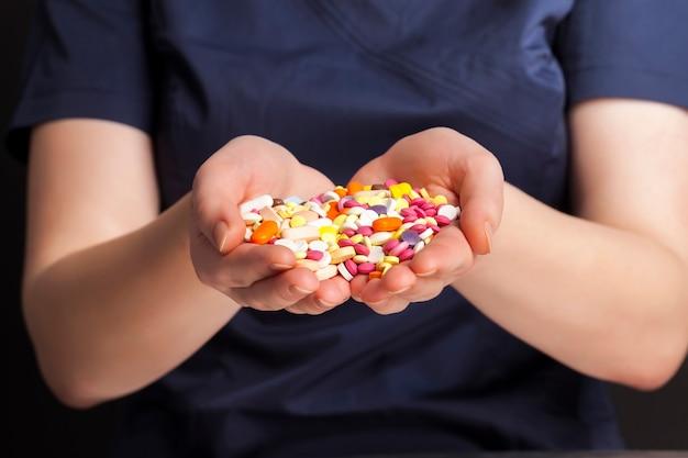 Un uomo in abbigliamento medico blu sta tenendo in mano un gran numero di pillole mediche