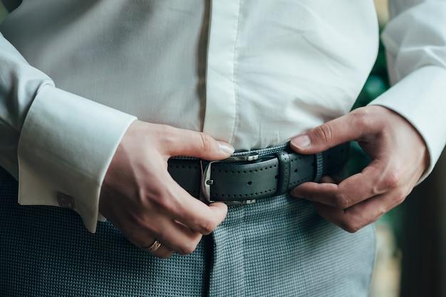 Un uomo in pantaloni blu e camicia bianca si abbottonava una cintura di pantaloni di pelle marrone