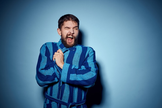 Un uomo in una veste blu su uno sfondo chiaro gesticola con le mani