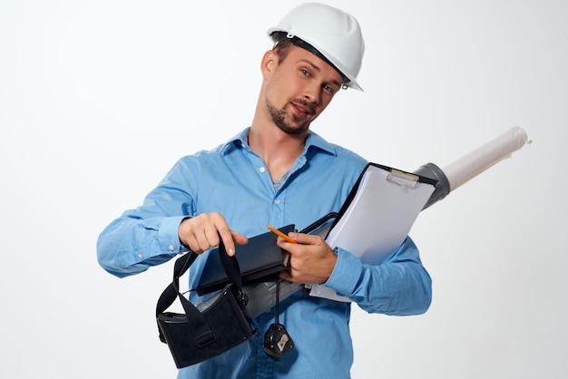 Un uomo con una camicia blu e un casco da costruzione progetti per professionisti della costruzione