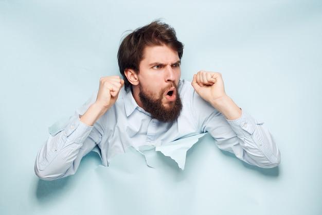 Uomo in camicia blu che sbircia dal primo piano dell'ufficio sullo sfondo
