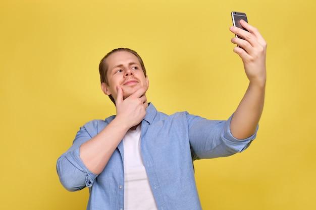 Un uomo in una camicia blu su uno sfondo giallo prende un selfie su uno smartphone per i social network.