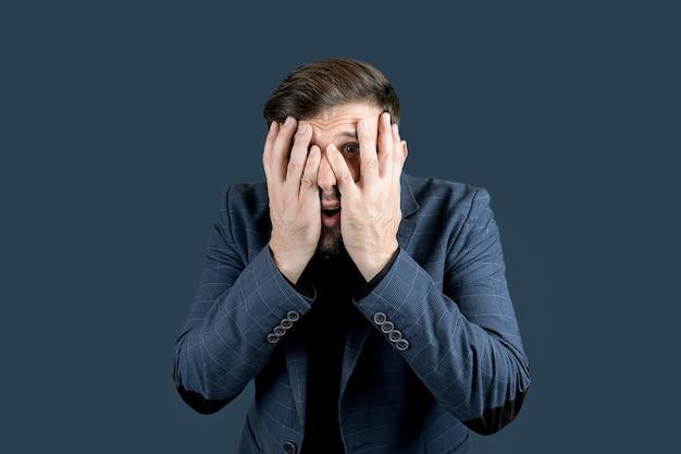 L'uomo vestito di blu si coprì il viso con entrambe le mani mostrando emozioni di paura