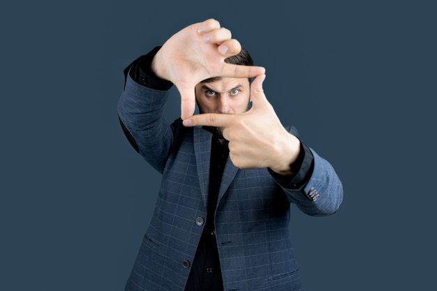 Un uomo vestito di blu fa una cornice con le dita e guarda attraverso le dita