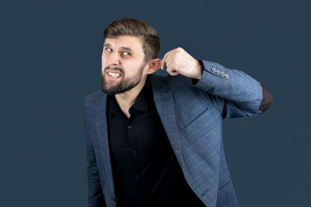 Un uomo vestito di blu si tira l'orecchio