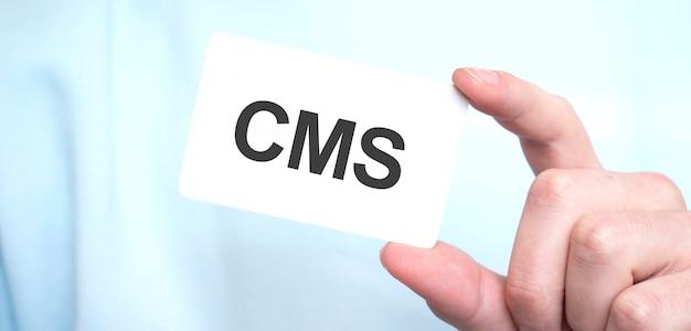 Uomo in felpa blu che tiene una carta con il testo cms, concetto di affari