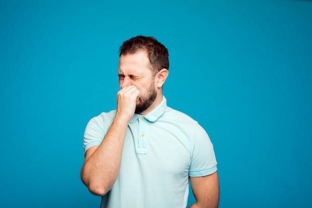 Un uomo con una maglietta blu su sfondo blu starnutisce in mano. concetto di allergia. prendi i farmaci per le allergie