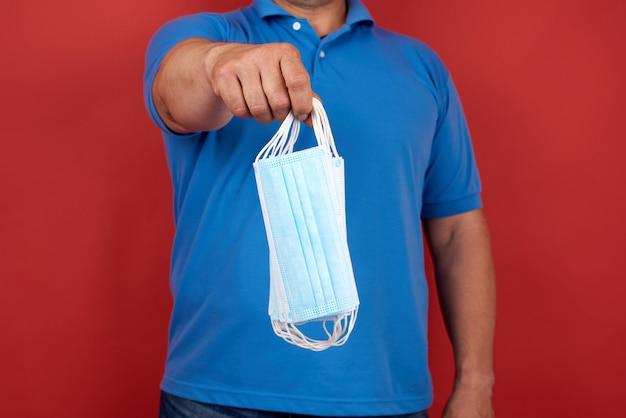L'uomo in una maglietta blu tiene una pila di maschere bianche mediche monouso