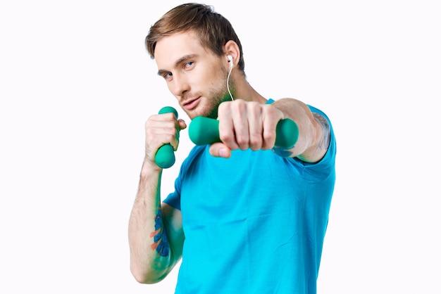 Uomo in maglietta blu con manubri in mano tatuaggio allenamento fitness