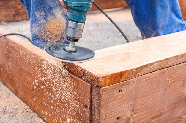 Un uomo in uniforme blu lavora la lavorazione del legno usando una smerigliatrice