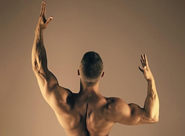 Culturista uomo con schiena muscolare solleva le mani bicipiti tricipiti sport fitness concetto di salute